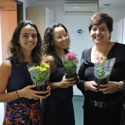 Três funcionárias seguram flores que ganharam para celebrar